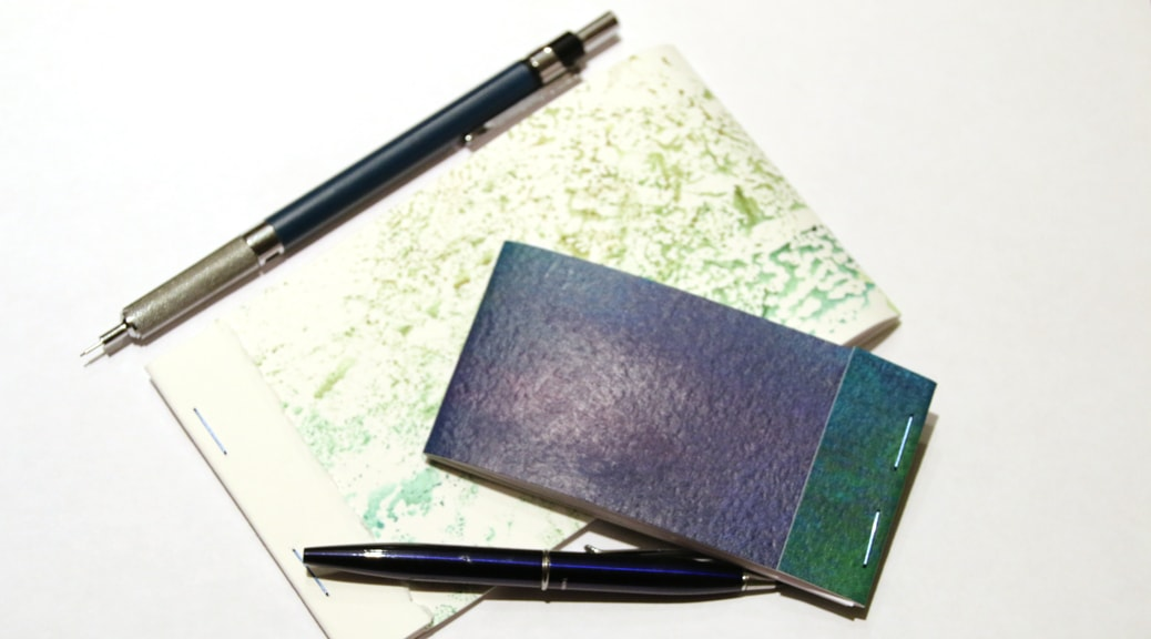 Two small matchbook-style journals.