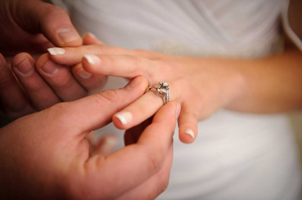Man putting diamond engagement ring on fiance's finger