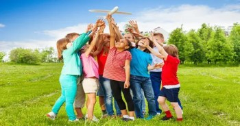 blog picture of children outside playing with a toy plane