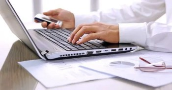 blog picture of laptop keyboard and a man's left hand on keys and right hand holding cell phone