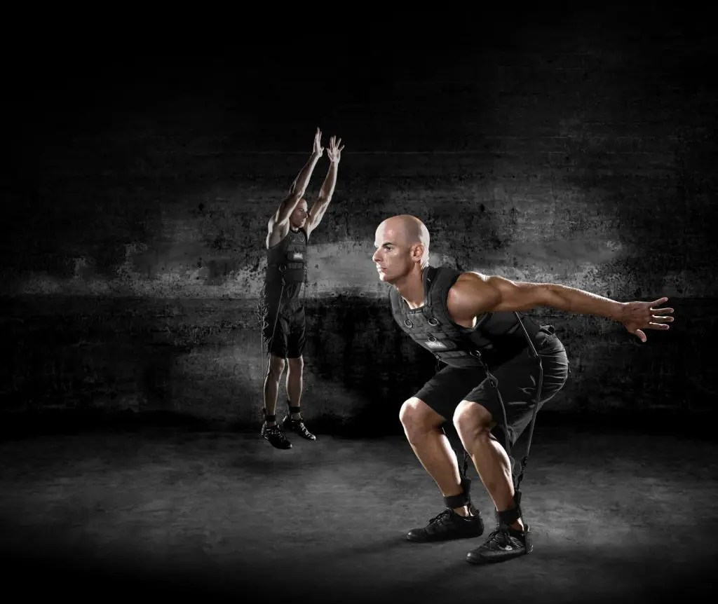 blog picture of two athletes doing jumps with a vest strapped to them with bands connected to the legs