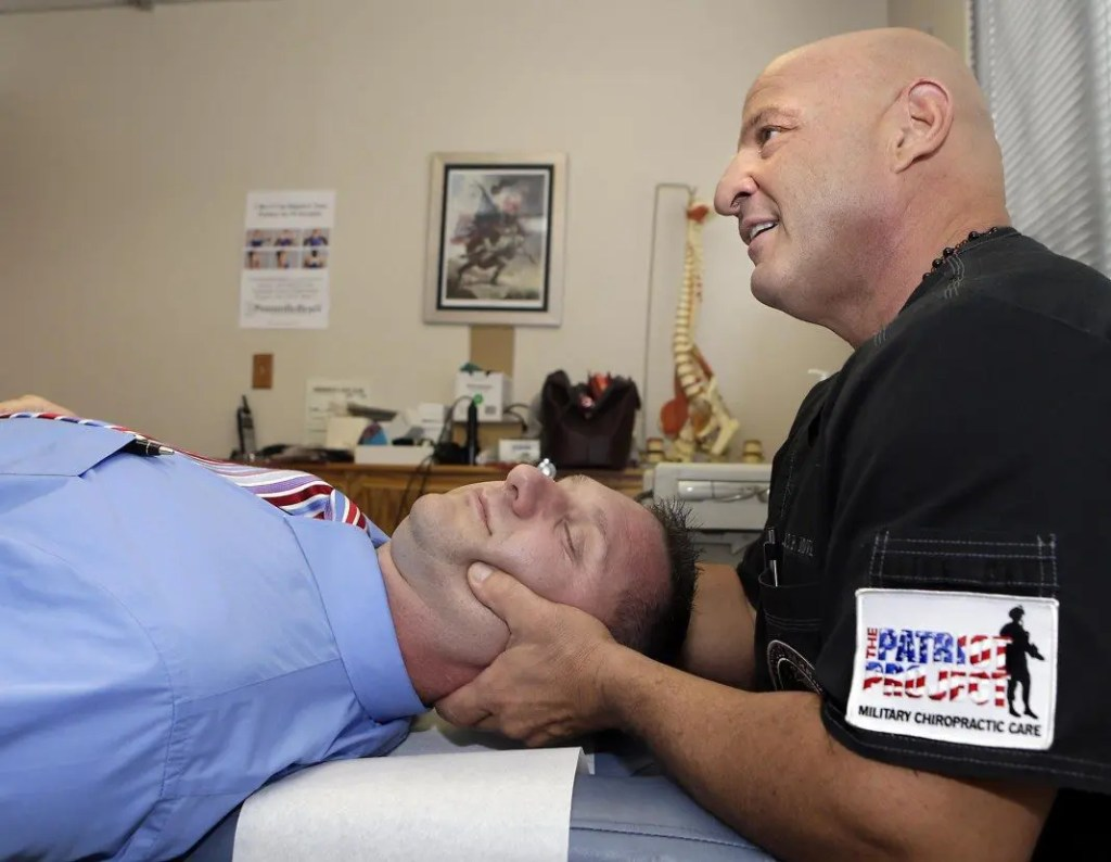 blog picture of chiropractor working on military service member