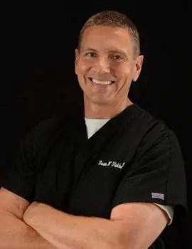 blog de imágenes de quiropráctico sonriente brazos cruzados