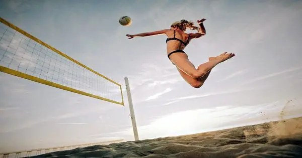 blog de imágenes de una dama jugando voleibol de playa que salta arriba por un pico