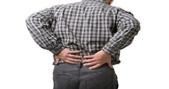 blog picture of a man standing holding his lower back in pain