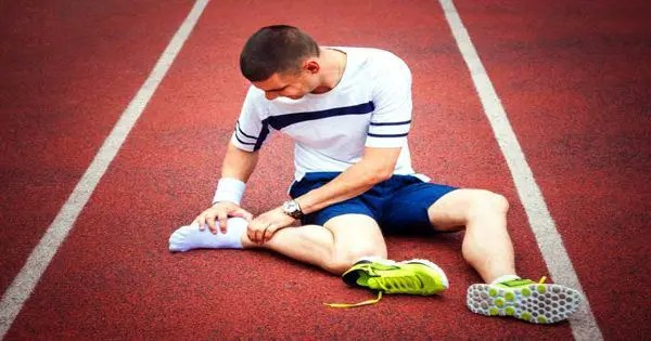 blog picture of runner on track shoe off grabbing foot in pain