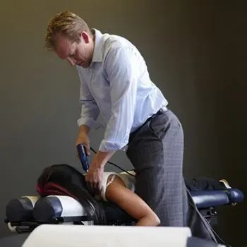 blog picture of chiropractor using machine to do an adjustment on lady's back