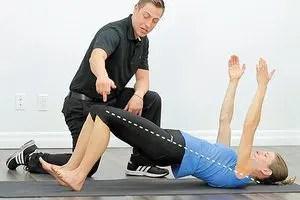 blog de imágenes del entrenador que trabaja con una señora que está colocando levantando sus pies parte inferior del cuerpo todavía en el suelo y los brazos levantados