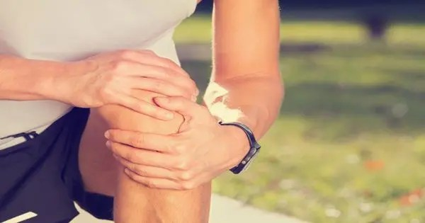 blog picture of male runner kneeling down grabbing knee with both hands