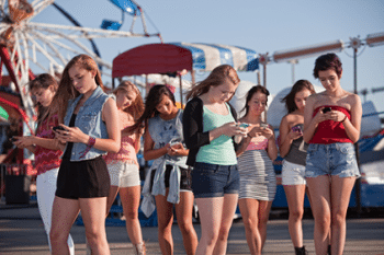blog picture of teenage girls at a carnival looking down at their phones