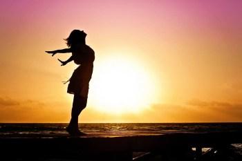 gambar blog wanita peregangan oleh lautan dengan matahari terbit