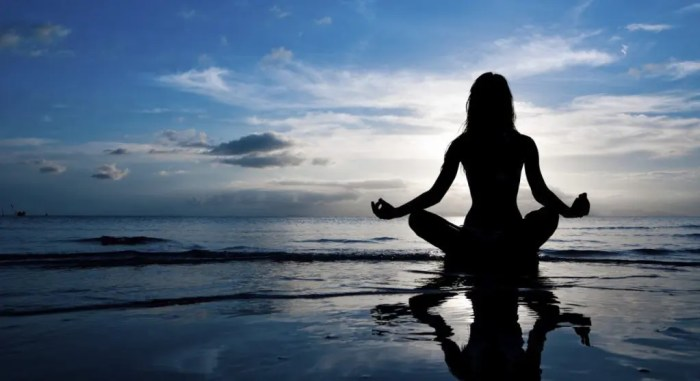 blog picture of lady meditating on beach during sunset