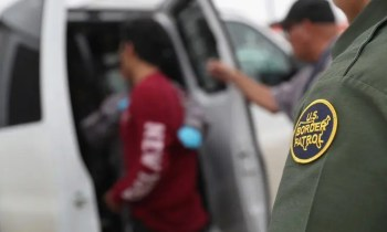 blog picture of border patrol agents taking in undocumented person