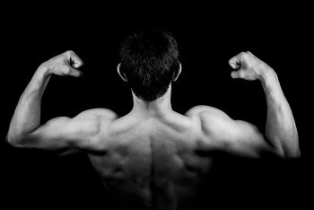 blog picture of man flexing muscles from the back