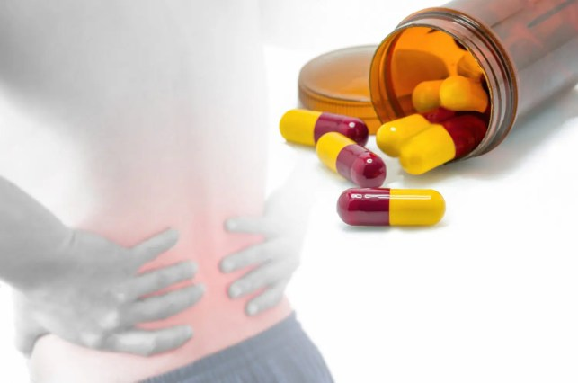 man grabbing lower back in pain and a bottle of pain medication open with capsules out of bottle
