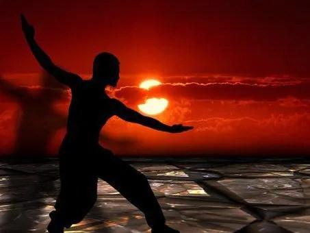 man doing tai chi behind the sun