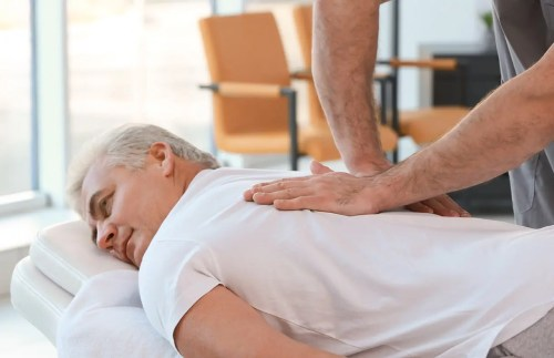 Image of an olden man receiving massage therapy to improve their migraine | El Paso, TX Chiropractor
