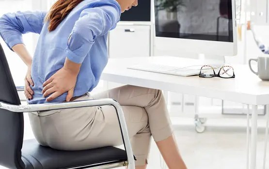 Woman holds her back as she experiences sciatica in the work setting.