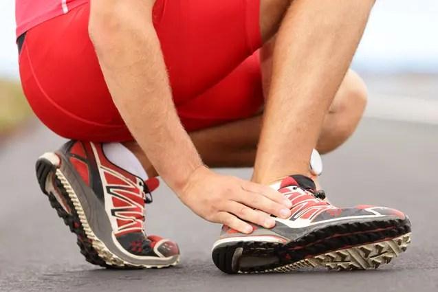 L'atleta maschio massaggia il suo piede a causa del dolore alla caviglia.