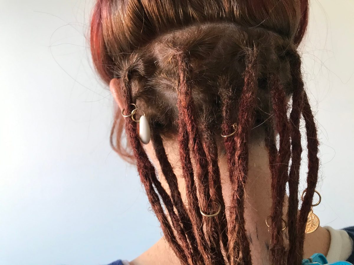 This image is a close-up of some partial dreadlocks, also called under dreadlocks, following a partial dreadlock installation. The dreadlocks are red and mid-length with pretty beads scattered throughout.
