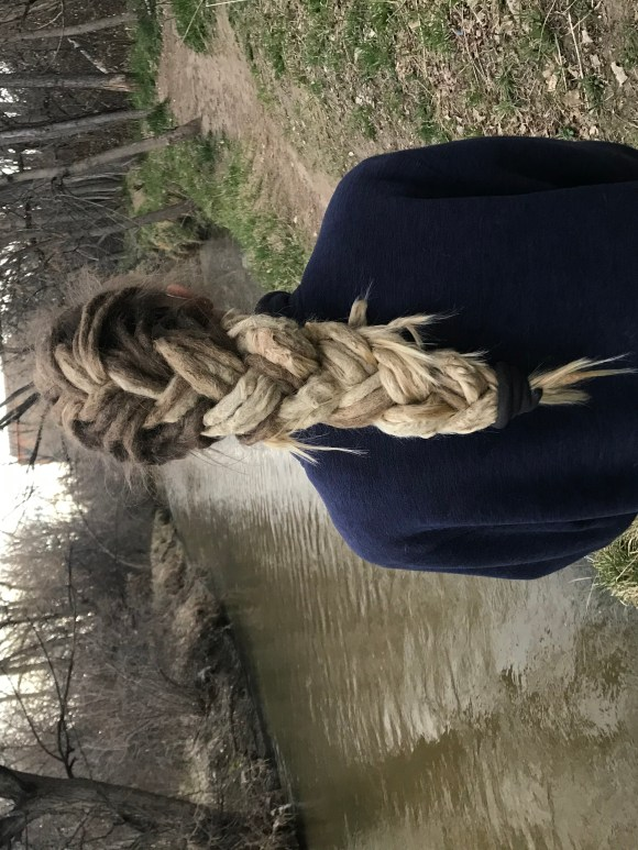 This image is a client photo that showcases a dreadlock braid style. The dreadlocks are long and blonde and my client is near a river.