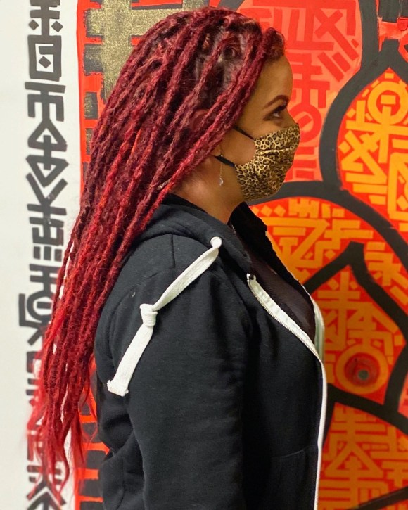 A client following a full dreadlock installation. She has long red dreads that are nearly waist-length.