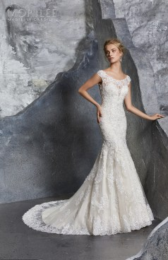 Keely Wedding Dress Romantic Fit and Flare Bridal Gown with Crystal Beaded Alençon Lace Appliqués on Net. A Wide Scalloped Hemline and Intricately Beaded Illusion Back Trimmed in Covered Buttons Completes the Look. Available in Three Lengths: 55″, 58″, 61″. Shown in Ivory/Champagne