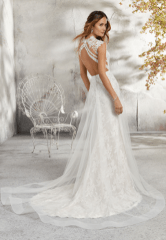 Lenore - Delicate and Romantic, this Chantilly Lace Wedding Dress is Accented with Venice Lace Appliqués and a Full Tulle Skirt Overlay. A Stunning Keyhole Back Trimmed in Covered Buttons Completes the Look.