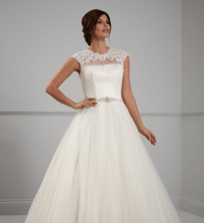 PC6301 Fabulous full tulle ball gown with embroidered lace appliques across shoulders and neck with illusion back and button detail. Pictured in ivory also available in white.