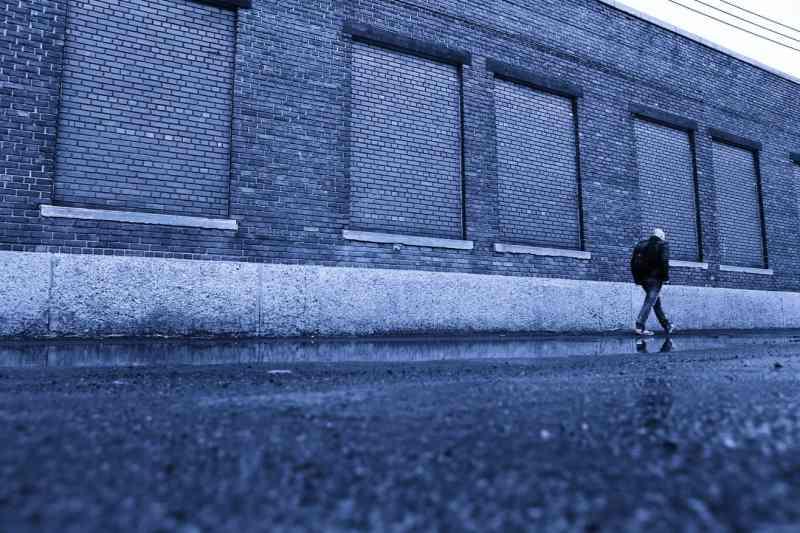 man walking in front of blue warehouse