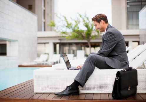 business man sitting outside hotel with laptop