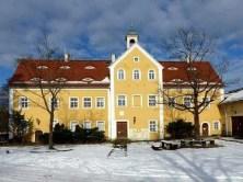 Außenansicht Jagdschloss Grillenburg mit Bäumen und Bänken