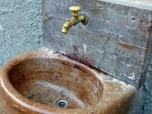 Waschbecken Stein goldener Wasserhahn