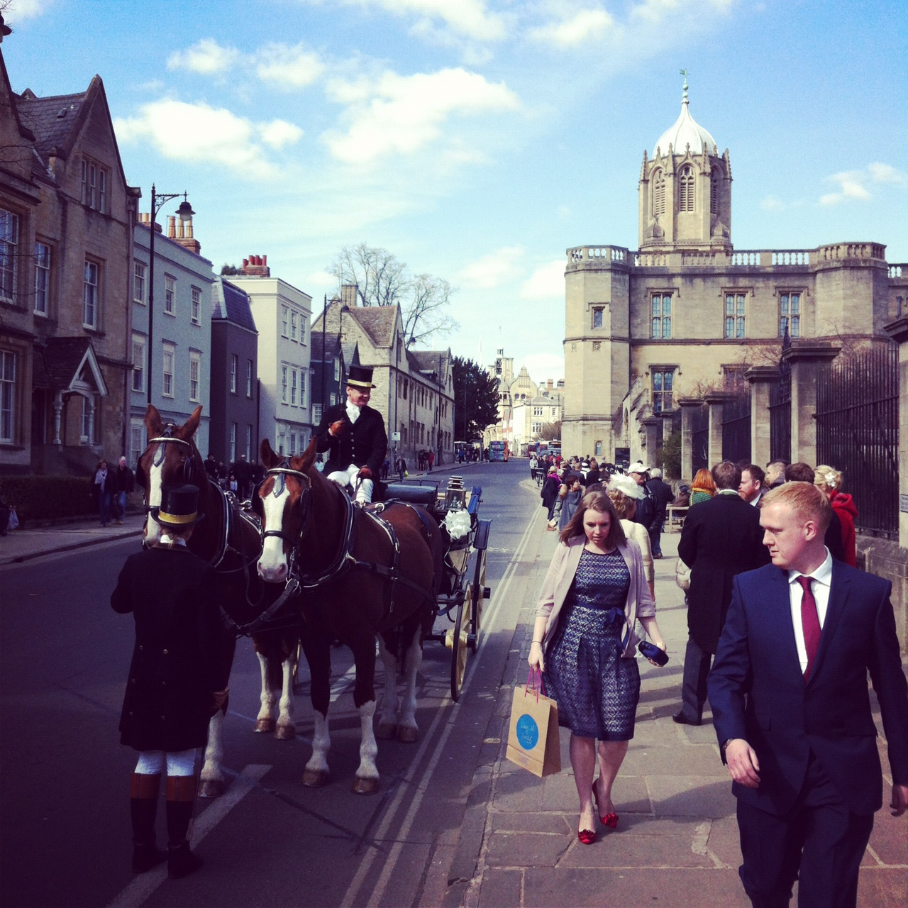 A horse and cart waiting to carry the bride and groom after their wedding at christchurch college oxford