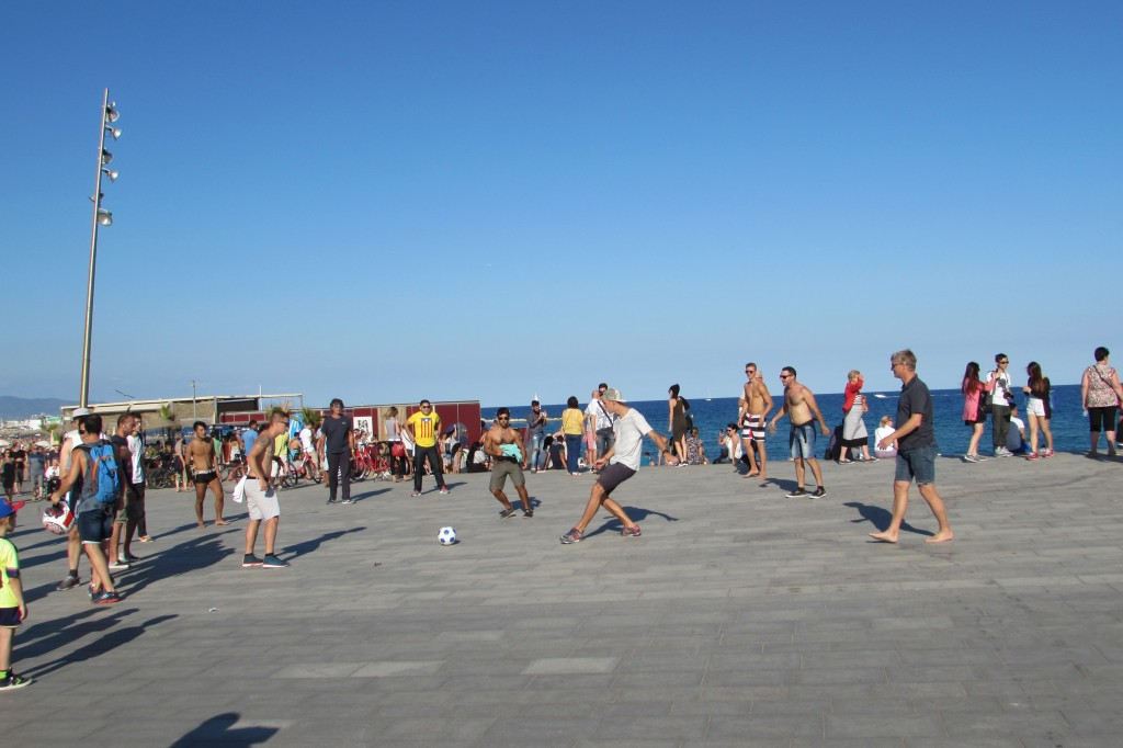 Tourists play street football at the beach in Barcelona
