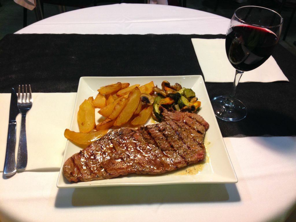 Dinner of champions Steak, grilled veggies and a glass of red wine from the Priorat red in Calella