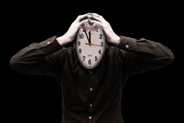 Man met handen aan het hoofd, het gezicht is een klok. Hij is gestresst.