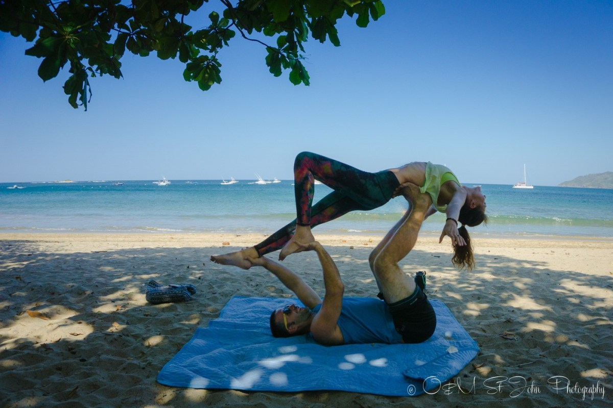 Max and Oksana doing acro yoga on the beach in Costa Rica