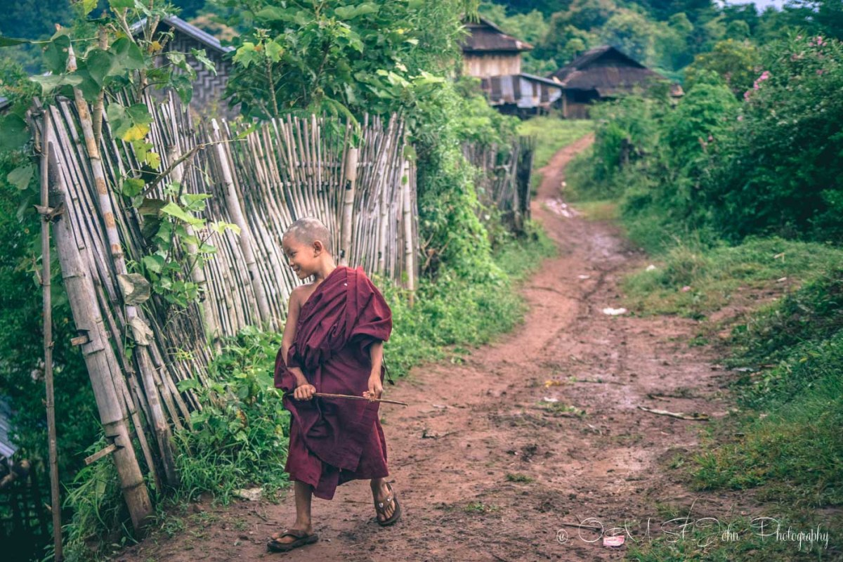 Novice Burmese monk walking down the street in village in Myanmar