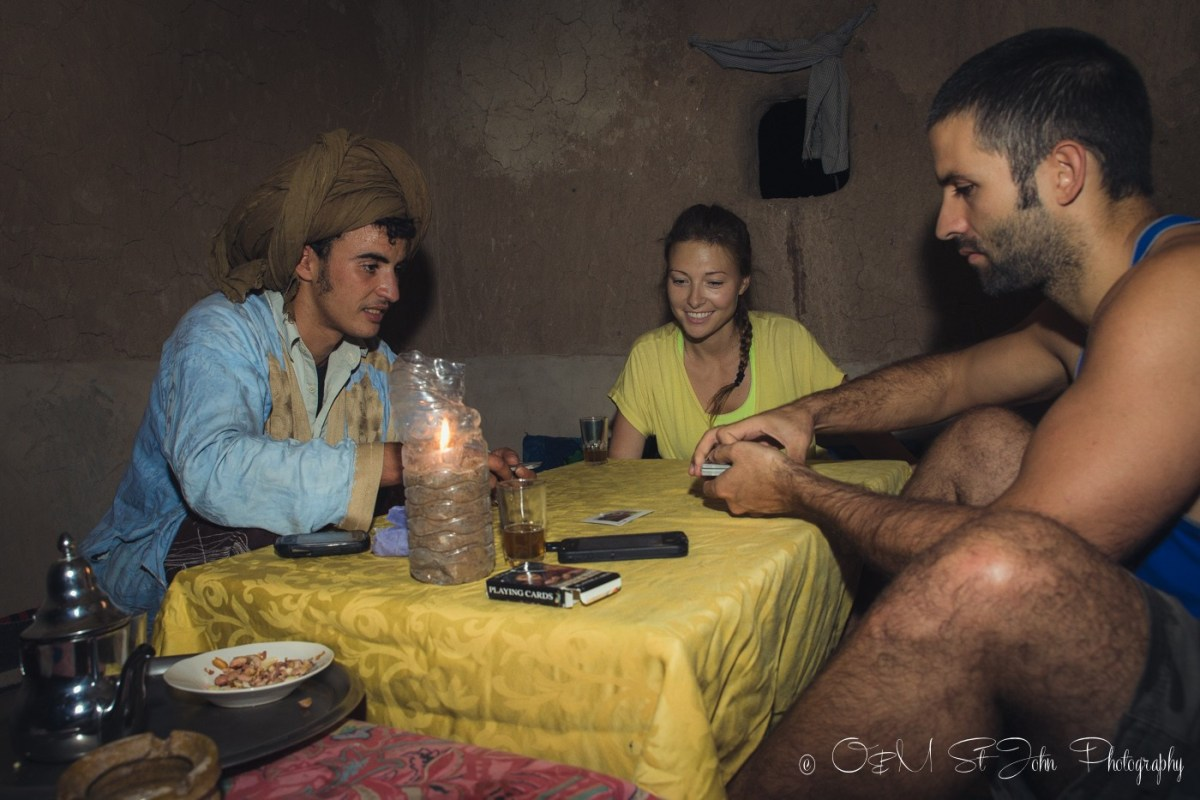 Max and Oksana playing cards with Muhamed in nomad hut in Erg Chebbi. Sahara Desert. Morocco