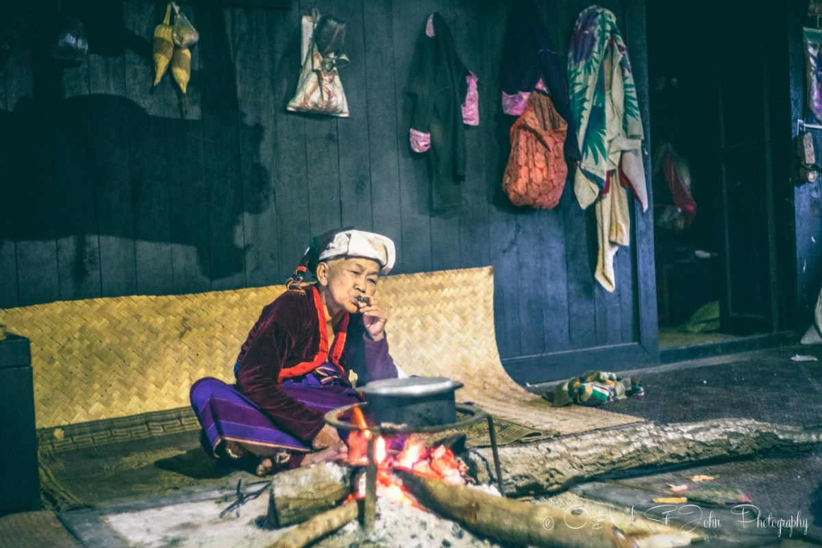 Elderly woman lights a cigar in her home in a village in Shan state, Myanmar