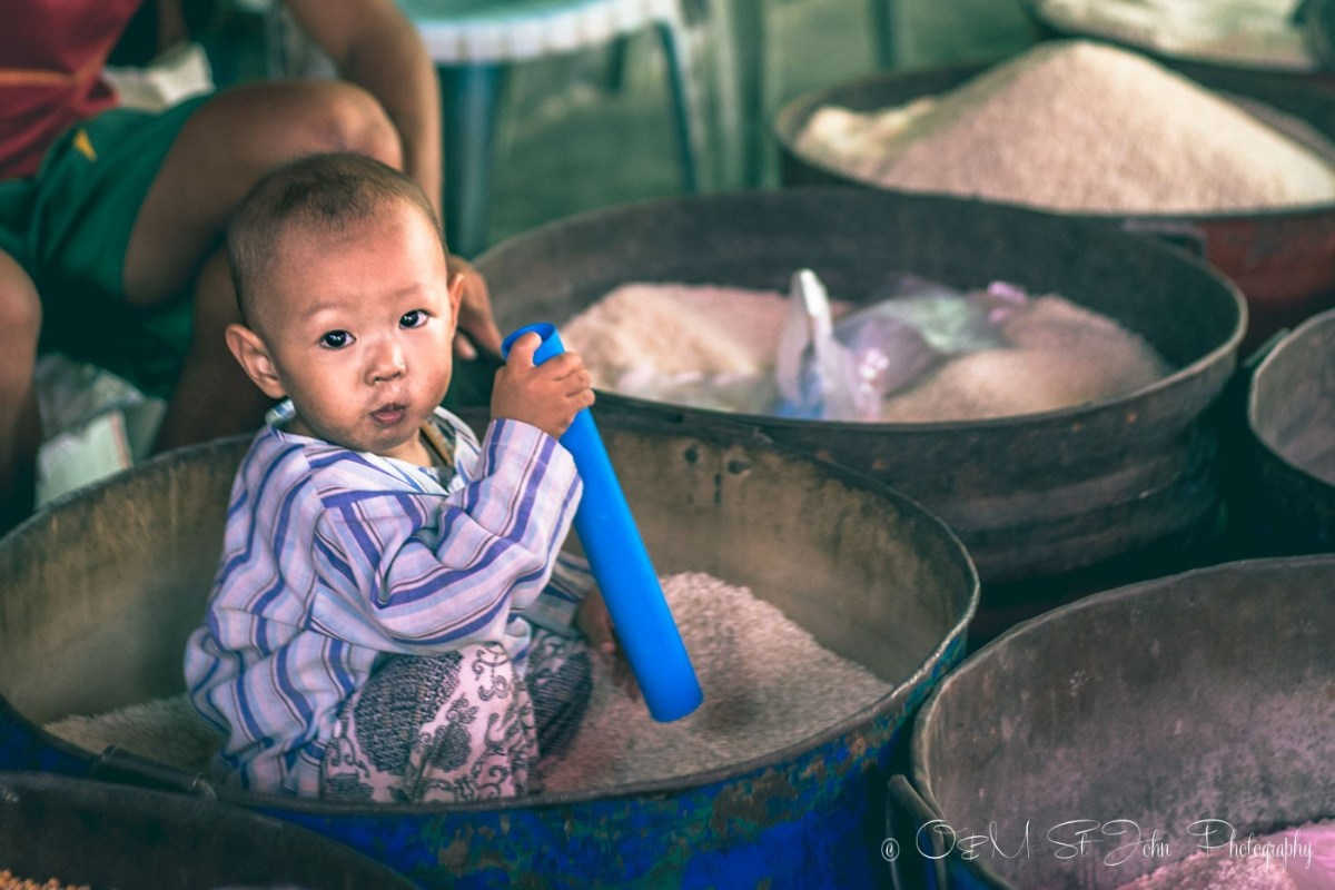 Baby in a rice bucket at the market in Myanmar