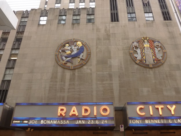 """The southern facade of the Music Hall, showing the Hildreth Meiere Medallions """"Dance"""" and """"Drama""""."""