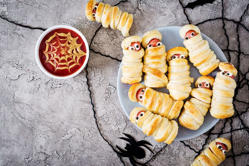 Scary sausage mummies in dough with funny eyes on table