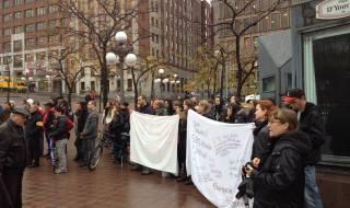 Photo : foule au bord du chapiteau de la Place D'Youville, tenant deux bannières blanches. La foule regarde une pièce de théâtre de rue.