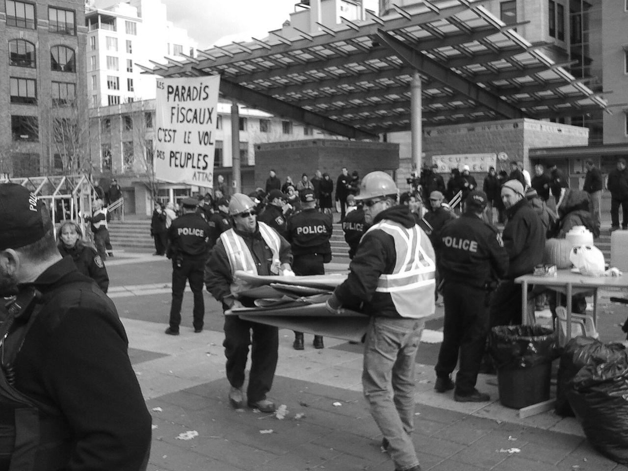 Les employés de la Ville de Québec et les policiers démantelant le camp des indignés en novembre 2011. PHOTO NATHALIE CÔTÉ