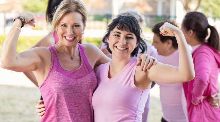 Women flexing their muscles at charity race breast cancer