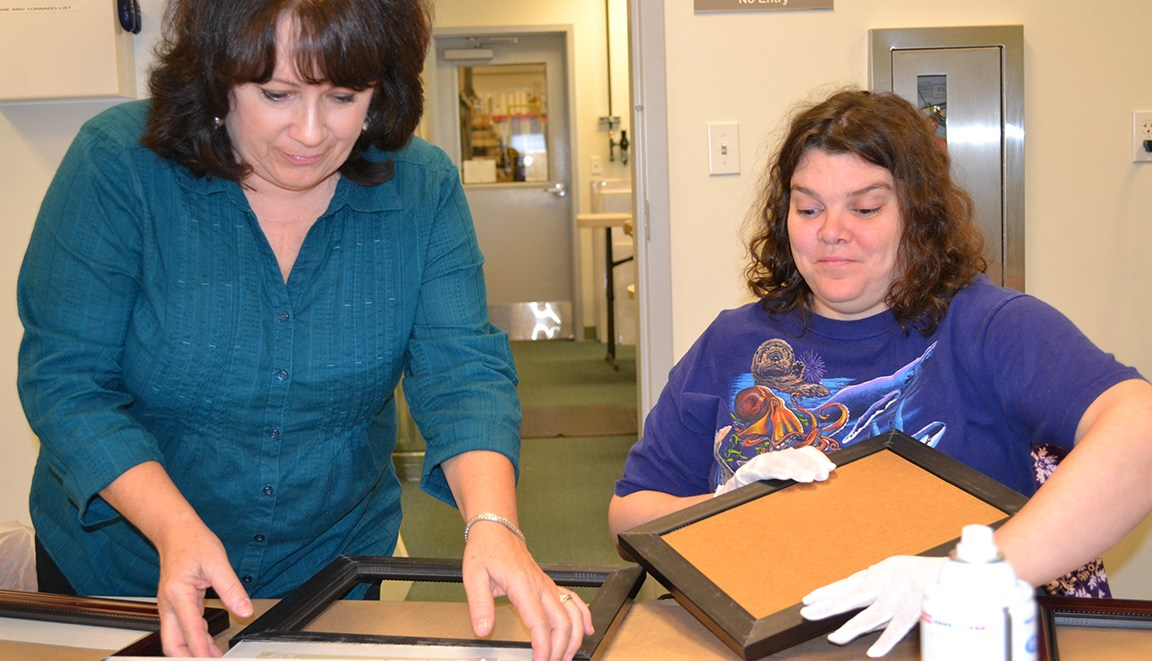 Carla (left) and Julie (right) work together on a project for Wyman Frame