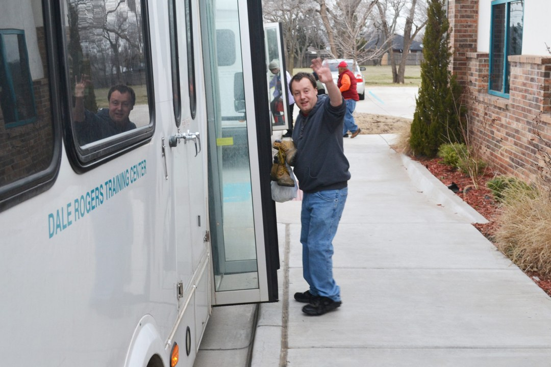 Bruce waves as he loads a bus to take him to his Mobile Workforce location.