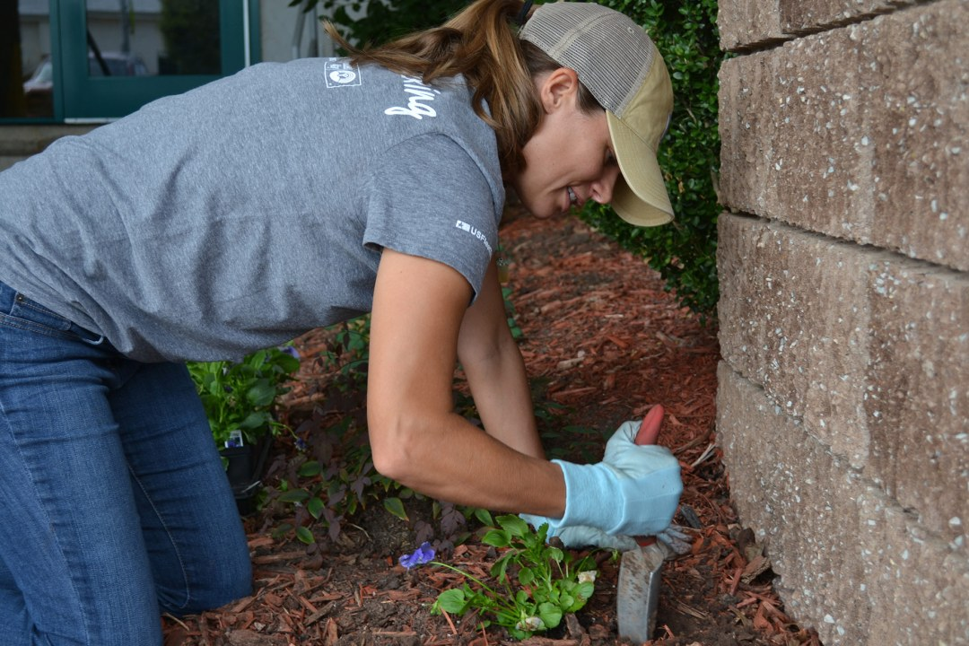 A volunteer with Tapstone Energy plants flowers at DRTC.